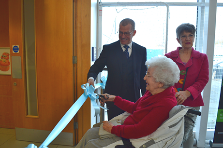 CEO Brian Carlin, Mary Tye cutting the ribbon and her daughter Leo